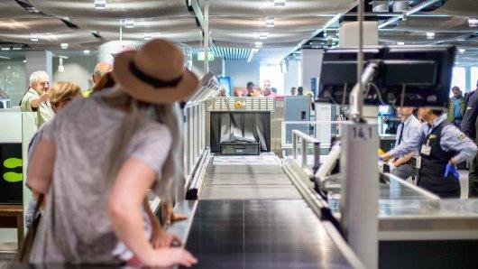 Eine Frau steht am 08.07.2016 am Flughafen Düsseldorf (Nordrhein-Westfalen) vor dem Abflug bei der Sicherheitskontrolle. Foto: Maja Hitij/dpa [ Rechtehinweis: (c) dpa ]