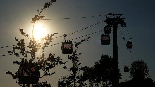 Die Gondeln der Seilbahn und Bäume sind am Abend im Licht der tiefstehenden Sonne am 06.08.2017 in Berlin auf der Internationalen Gartenausstellung ´IGA Berlin 2017» zu sehen. Noch bis zum 15. Oktober 2017 findet die IGA unter dem Motto ´Ein MEHR aus Farben» statt.