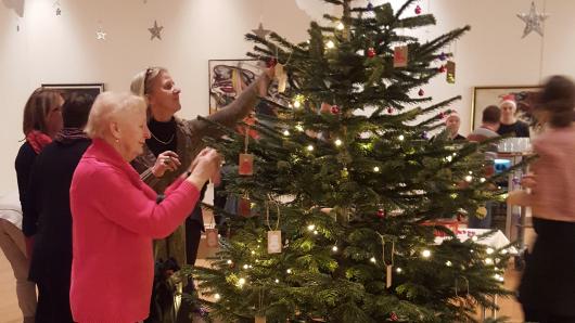 Caritas-Gäste schmücken gemeinsam mit WestLotto-Mitarbeitern den Weihnachtsbaum.