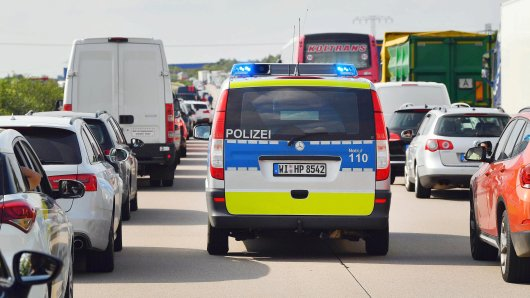 Ein Polizeiauto fährt während eines Staus in einer Rettungsgasse an Autos und Lastkraftwagen vorbei.