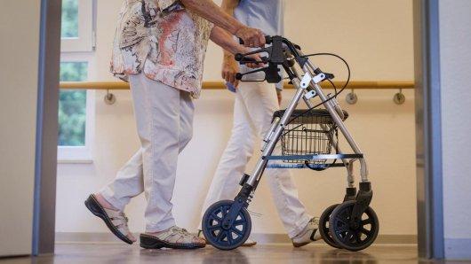 Eine Pflegekraft geht in einem Pflegeheim mit einer älteren Dame über einen Korridor. Der Bundesrat stimmte heute der vom Bundestag beschlossenen Anhebung des Beitragssatzes der Pflegeversicherung zu.
