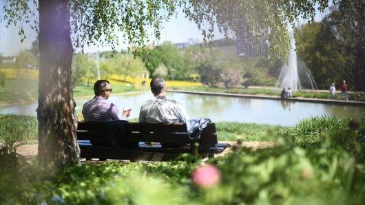 Zwei Männer sitzen während ihrer Mittagspause auf einer Bank im Schatten.