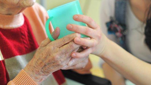 Eine Pflegekraft hilft einer alten Frau beim Trinken aus einem Becher in einem Seniorenheim. Private Pflege-Anbieter fordern eine bessere Bezahlung für Fachkräfte.