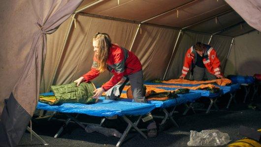 Bevor das Zelt um 21 Uhr für die Wohnungslosen öffnet, werden die Betten von den Ehrenamtlichen aufgestellt und bezogen.
