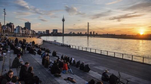 Menschen sitzen bei Sonnenuntergang am Rhein. Was muss Nordrhein-Westfalen tun, um noch mehr Touristen ins Land zu locken? Welche Möglichkeiten bietet dabei die Digitalisierung? Antworten soll eine neue Tourismusstrategie geben.