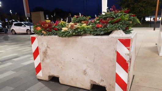 Mehrere Grabgestecke hübschen den Betonklotz im Ruhrpark in Bochum auf.