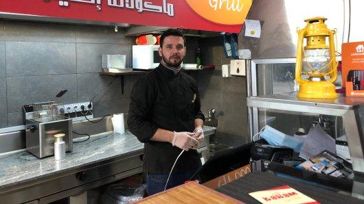 Rewar Ayoub hinterm Grill. Der Syrer ist 2015 nach Deutschland gekommen, liebt seinen Job.