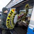 Polizisten stellen bei einer Durchsuchung verbotenen Satudarah Symbole sicher.