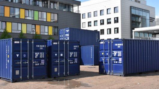 Container werden auf dem Gelände der Uniklinik zu einer Schutzmauer zusammengestellt.