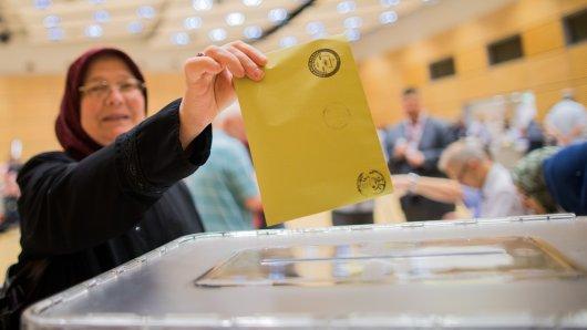 Die Wahlberechtigte Hatice Güner wirft ihren Wahlzettel in die Urne. Hier geben in Deutschland lebende Türken ihre Stimme für die türkischen Parlaments- und Präsidentenwahlen ab.