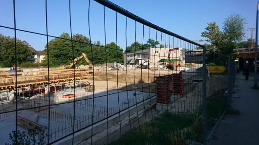 Im Hintergrund ist der fertige Bau des Kindergartens schon zu erkennen. Bagger sind derzeit im Außengelände im Einsatz.