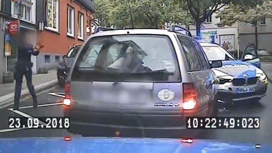 Ein Polizist stellt mit gezückter Pistole den Rowdy, der durch die Essener City geflüchtet ist.