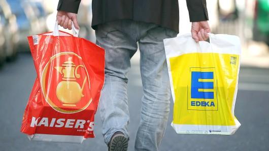 """ARCHIV- ILLUSTRATION - Ein Mann geht am 09.09.2015 in Köln (Nordrhein-Westfalen) mit jeweils einer Tragetasche der Supermarktketten Kaisers's Tengelmann und Edeka über die Straße. Bundeswirtschaftsminister Gabriel (SPD) und der Verdi-Vorsitzende Bsirske werden am 31.10.2016 ein Statement """"zum Thema Ministererlaubnis zu Edeka/Kaiser's Tengelmann"""" abgeben. Foto: Oliver Berg/dpa +++(c) dpa - Bildfunk+++"""