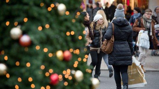 Passanten gehen vorbei an weihnachtlicher Dekoration einkaufen.