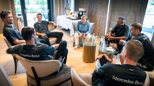 Bundeskanzlerin Angela Merkel (Mitte) trifft (von links unten im Uhrzeigersinn) Sami Khedira, Mats Hummels, Thomas Müller, Jerome Boateng, Manuel Neuer und Toni Kroos.