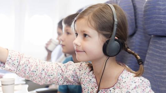 Ein Mädchen mit Kopfhörern auf dem Bord eines Flugzeugs. (Symbolbild)
