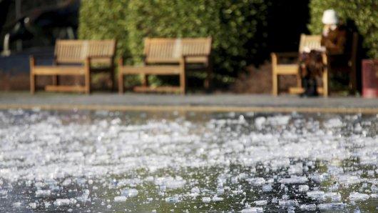 Hinter den Eisschollen auf einem Teich in der Gruga sitzt eine Spaziergängerin auf einer Parkbank in der Sonne. Das sonnige aber eiskalte Wetter soll auch in den nächsten Tagen anhalten.