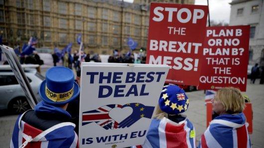 Anti-Brexit-Demonstrant Steve Bray (l) demonstriert gegenüber dem Parlament mit Plakaten. Auch für NRW-Unternehmen wäre der Deal ein Rückschlag.