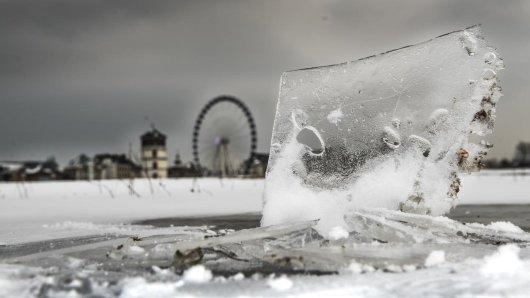 Eisschollen stehen aus einer Pfütze am Rheinufer in Düsseldorf Obekassel empor.