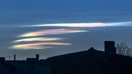 Seltsamen Phänomen: Leuchtende Nachtwolken über den Dächern einer Stadt.