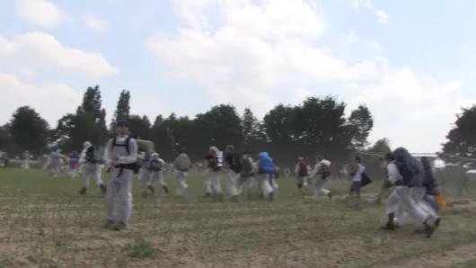Klima-Aktivisten durchbrechen auf dem Weg zum Tagebau Garzweiler eine Polizeisperre und stürmen über einen Acker.