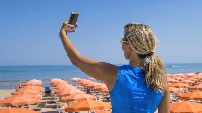 Frau macht Urlaub-Selfie: Im Hintergrund lauert eine
