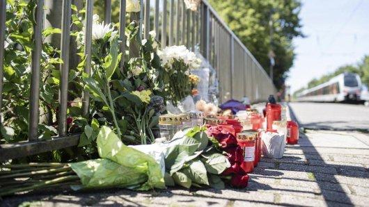 Trauernde haben nach der unfassbaren Tat in Voerde (NRW) Blumen und Kerzen am Bahnsteig niedergelegt.