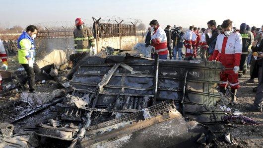 Rettungskräfte betrachten die Trümmerteile nach dem Flugzeugabsturz im Iran.