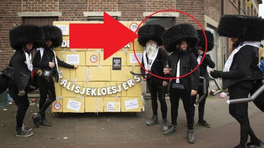 """Mitglieder der Gruppe """"De Kalisjekloesjers"""" stehen bei einem Karnevalsumzug in Belgien neben einer Attrappe der Klagemauer und haben sich als orthodoxe Juden verkleidet."""