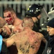 Blutüberströmte Hooligans werden von der Polizei abgeführt.