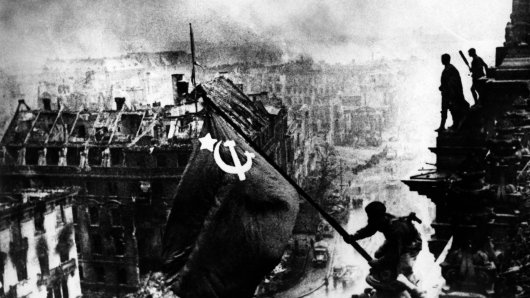 Apr 30 1945 Berlin GERMANY Soviet soldier hoisting the Soviet flag on the burnt out building of