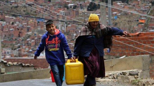 Anwohner tragen einen Wasserkanister zu ihrem Haus. In Bolivien sind die Wasservorräte derzeit extrem knapp. Touristen sollten vorab im Hotel fragen, ob es genügend Wasser gibt.