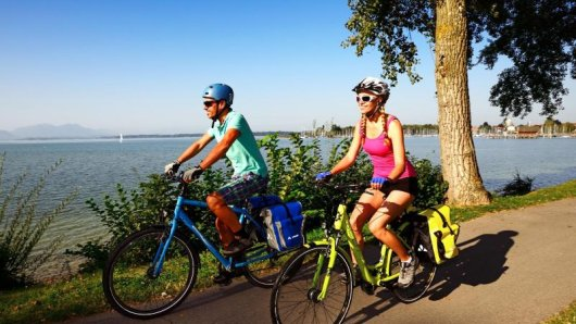 Auf zwei Rädern um den Chiemsee - wie hier bei Seebruck erkunden viele Touristen das Bayerische Meer gerne vom Fahrradsattel aus.