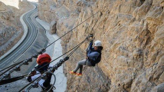 Urlauberin auf der Zipline in der Via Ferrata in Ras al Khaimah:Die Berge sind der Faktor, der das kleine Emirat vonDubai und Abu Dhabi abhebt.