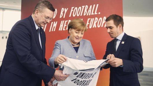Bundeskanzlerin Angela Merkel (M) bekommt anlässlich der Bewerbung für die Fußball-EM 2024 von DFB-Präsident Reinhard Grindel (l) und EM-Botschafter Philipp Lahm ein Trikot überreicht.