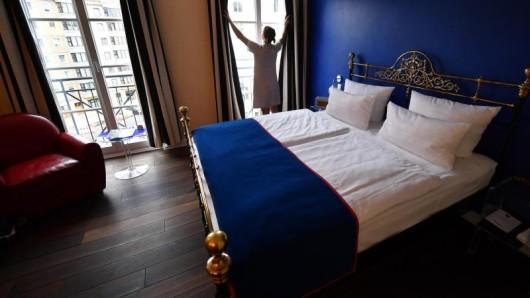 Wie hier im Boutique- und Design-Hotel The Dude in Berlin lassen sich Hotelbetten mit einem Bettschal regelrecht in Szene setzen. Doch das Accessoire dient auch der Hygiene.