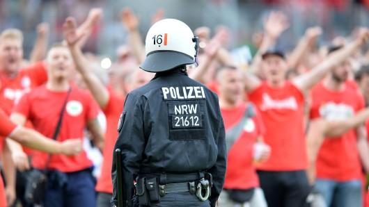 Ein Polizist sichert das Spielfeld beim Platzsturm der RWO-Fans.