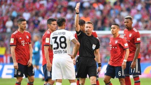 Schiedsrichter Tobias Welz (M) zeigt die Rote Karte gegen den Leverkusener Karim Bellarabi (38) für das Foul an Rafinha.