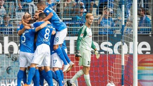Bochums Spieler jubeln, während Ingolstadts Torwart Marco Knaller enttäuscht den Ball aus dem Tor holt.