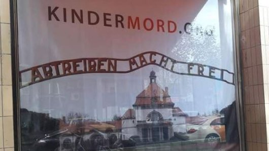 """Das Schaufenster einer Kölner Buchhandlung zeigt ein Plakat mit der Aufschrift: """"Abtreiben macht frei""""."""