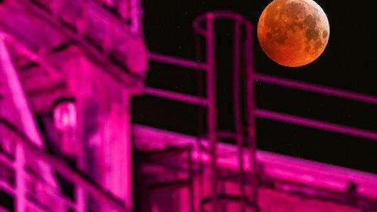 """Als roter, sogenannter """"Blutmond"""" präsentiert sich der Vollmond neben einem angestrahlten Hochofen im Landschaftspark Duisburg, während er in den Kernschatten der von der Sonnen angestrahlte Erde tritt. Der Kernschatten verdeckt dabei die sichtbare Oberfläche des Mondes. Mond, Sonne und Erde stehen genau in einer Linie."""