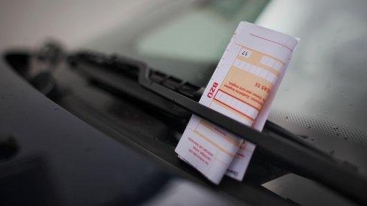 Ein Strafzettel  steckt im Scheibenwischer eines geparkten Autos. In Essen wurden im vergangenen Jahr rund ein Viertel weniger Knöllchen verteilt als im Vorjahr.