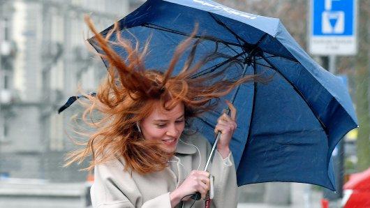 Eine junge Frau mit Regenschirm kämpft im Regen gegen den Wind an.