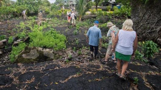 Touristen laufen über erkaltete Lava, zwischen der schon wieder Pflanzen sprießen. Der Ausbruch liegt mehr als ein Jahrhundert zurück.