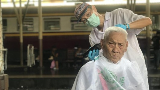 Auf dem Hauptbahnhof Hua Lamphong schneidet ein Friseur einem älteren Mann die Haare. Der Haarschnitt ist kostenlos.