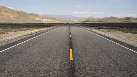 Eine schmaler werdende Linie, die sich irgendwo in den Bergen am Horizont verläuft: der U.S. Highway 50 in Nevada.