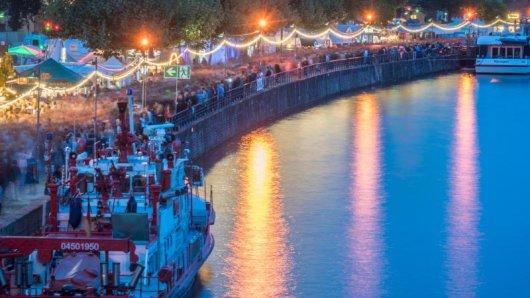 Menschenmassen strömen beim Museumsuferfest über die bunt beleuchteten Uferbereiche des Main.