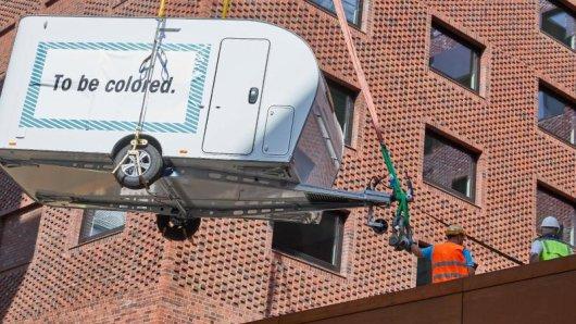 Ein Kran hebt einen Wohnwagen auf die Terrasse vom Hotel Pierdrei in der Hamburger Hafencity.