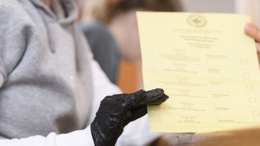 Eine Wahlhelferin in Bayern arbeitet mit Handschuhen.
