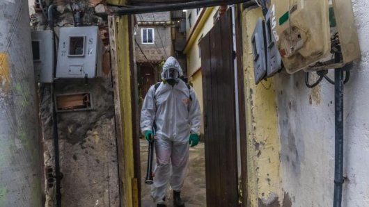 Ein Mann mit Schutzkleidung und einem Gerät zur Straßendesinfektion in einem Armenviertel von Rio de Janeiro.